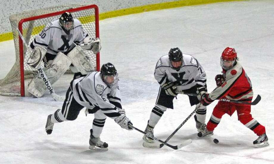 """Special to the Press 02.22.12 Xavier's Shane Baldwin covers the puck as John Burkinshaw restrains Conard's Nick Haggerty in Wednesday's game. Xavier won, 5-2. To buy a glossy print of this photo and more, visit <a href=""""http://www.middletownpress.com"""">www.middletownpress.com</a>. / a"""