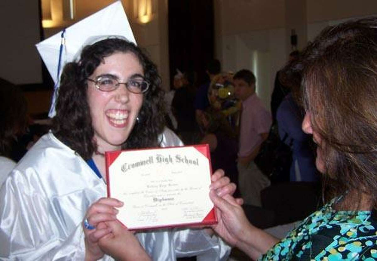 An elated Brittany Greider of Cromwell shows her diploma to her proud mother, Judy Mazzotta, also of Cromwell.