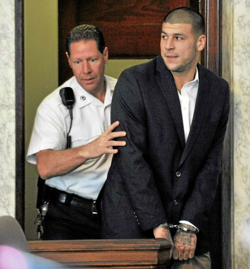 In this Aug. 22, 2013, file photo, former New England Patriots NFL football player Aaron Hernandez, is lead into court in Attleboro, Mass. Hernandez, who has been indicted on a murder charge in the killing of Odin Lloyd, is scheduled to face arraignment in Superior Court Friday, Sept. 6, 2013 in Fall River, Mass. (AP Photo/Josh Reynolds, File) Photo: AP / FR25426 AP