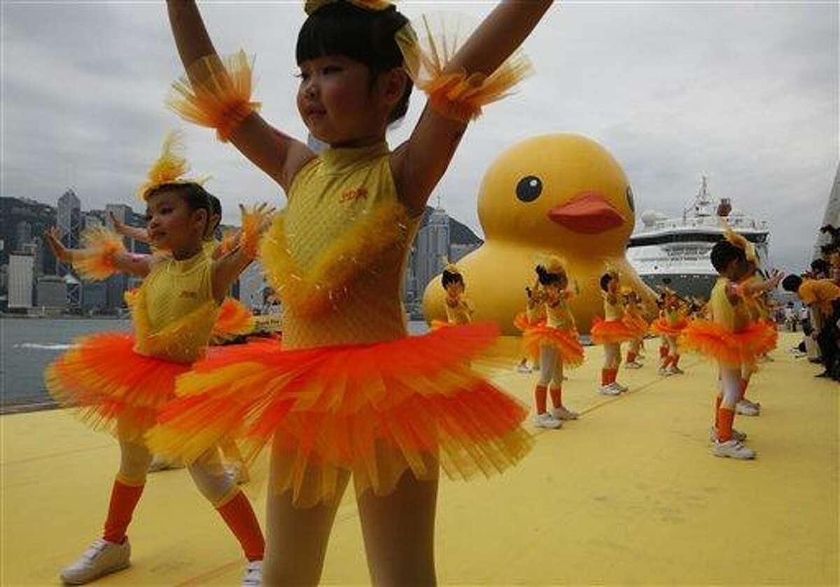 Dancers perform during a welcoming ceremony of a giant Rubber Duck created by Dutch artist Florentijn Hofman in Hong Kong Thursday, May 2, 2013. Since 2007 the 16.5-meter (54-feet)-tall Rubber Duck has traveled to various cites including Osaka, Sydney, Sao Paulo and Amsterdam. (AP Photo/Kin Cheung)