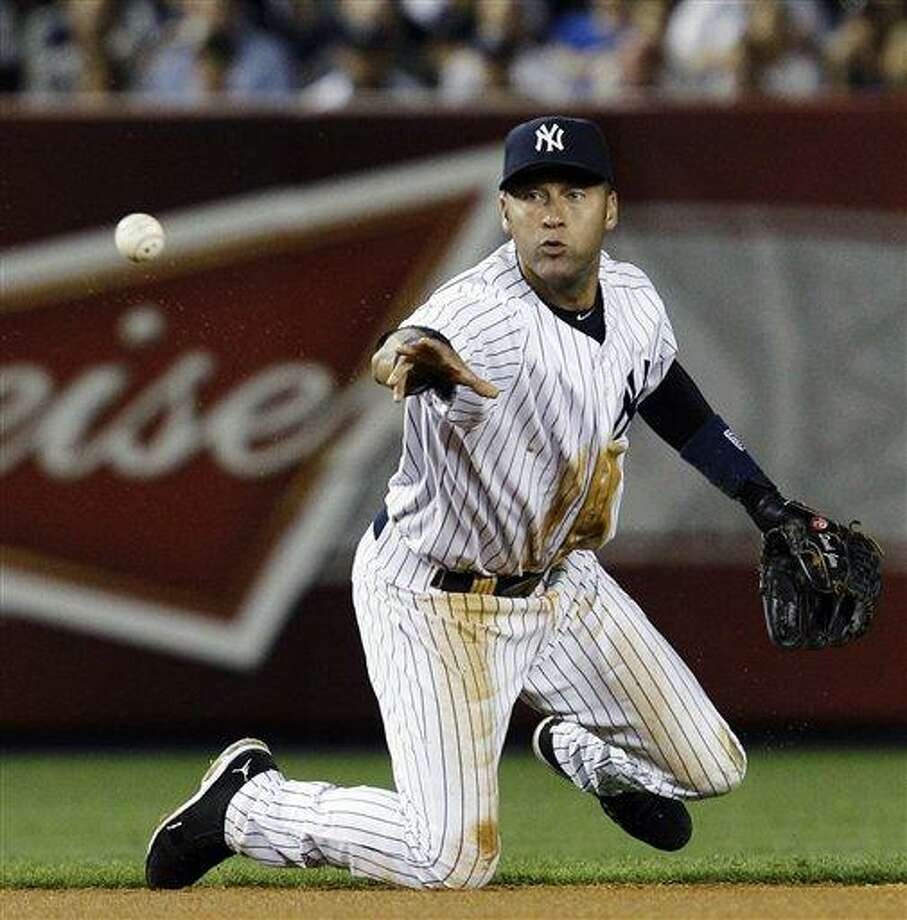 New York Yankees shortstop Derek Jeter throws to second baseman Robinson Cano, who forced out Atlanta Braves' David Ross after Michael Bourn hit into a seventh-inning fielder's choice, during their baseball game at Yankee Stadium in New York, Monday, June 18, 2012. (AP Photo/Kathy Willens) Photo: ASSOCIATED PRESS / AP2012