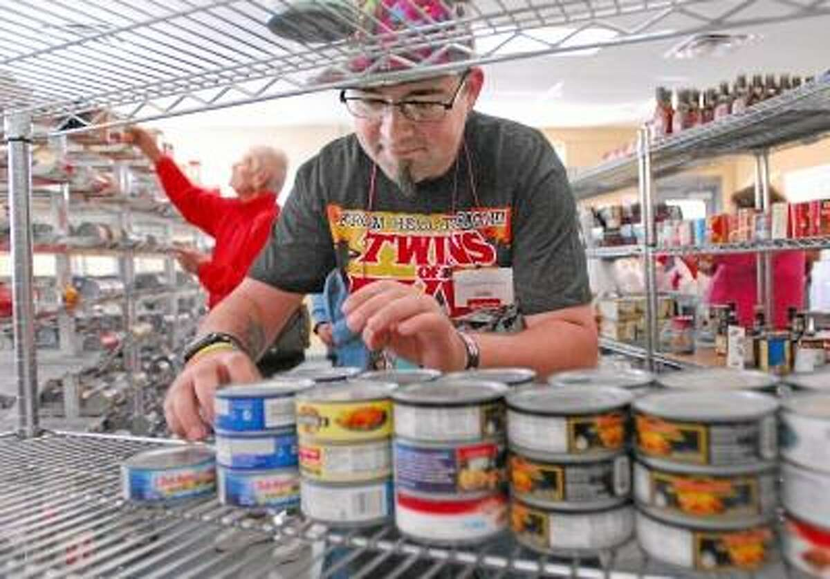 CATHERINE AVALONE/THE MIDDLETOWN PRESS Middletown resident John Kovach, a volunteer at Amazing Grace Food Pantry in Middletown organizes cans of tuna fish Monday afternoon, just a few days before the Amazing Challenge Soup Supper which will be held Thursday from 5 - 7 p.m. at the Fox Parish Center at St. Francis of Assisi Church on 10 Elm Street in Middletown.