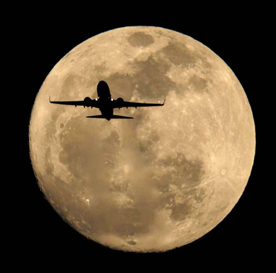 A Southwest Airlines jet is silhouetted against the rising full moon as it takes of from Sky Harbor Airport Sunday, Feb. 24, 2013 in Phoenix. (AP Photo/Charlie Riedel) Photo: ASSOCIATED PRESS / The Associated Press2013