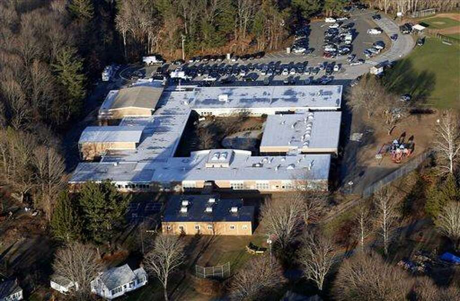 FILE - This Dec. 14, 2012 aerial file photo shows Sandy Hook Elementary School in Newtown, Conn., where a gunman shot 27 people dead, including 20 children. The Sandy Hook School Building Task Force meets Friday night, May 3, 2013, to debate whether to renovate or rebuild on the existing school site, or to construct a new school building on nearby property.  (AP Photo/Julio Cortez, File) Photo: AP / AP