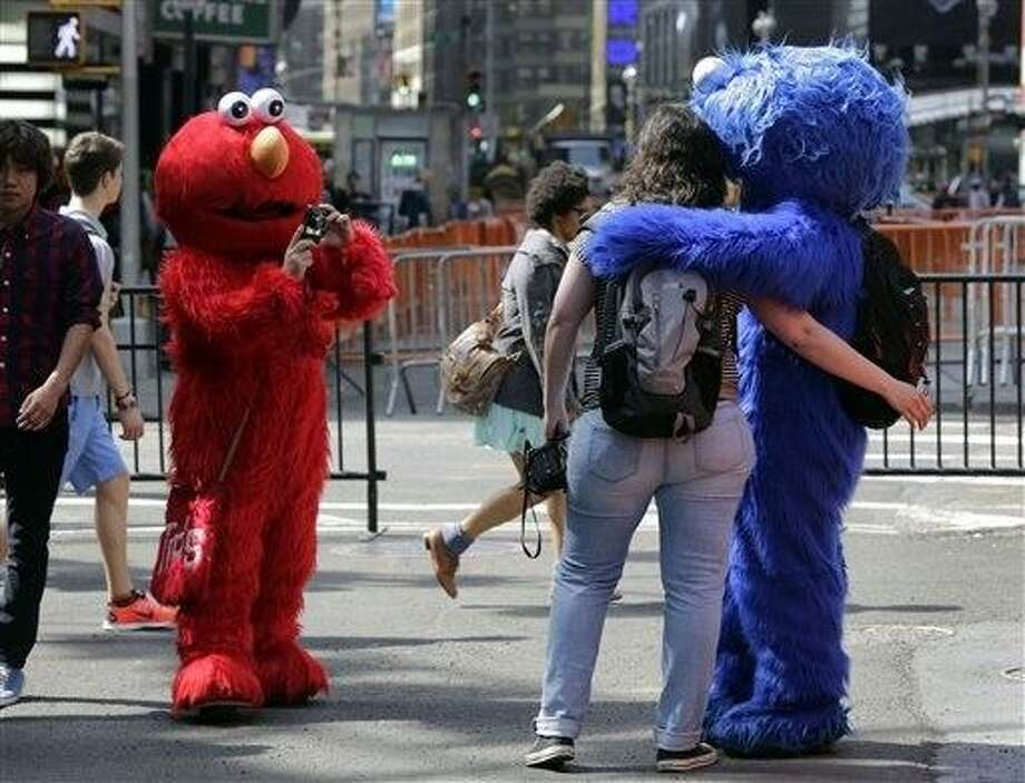 An Elmo character, left, uses a woman's camera to photographer her with a Cookie Monster character, in New York's Times Square, Tuesday, April 9, 2013.  A string of arrests in the last few months has brought unwelcome attention to the growing number of people, mostly poor immigrants, who make a living by donning character outfits, roaming Times Square and charging tourists a few dollars to pose with them in photos. (AP Photo/Richard Drew) Photo: AP / AP
