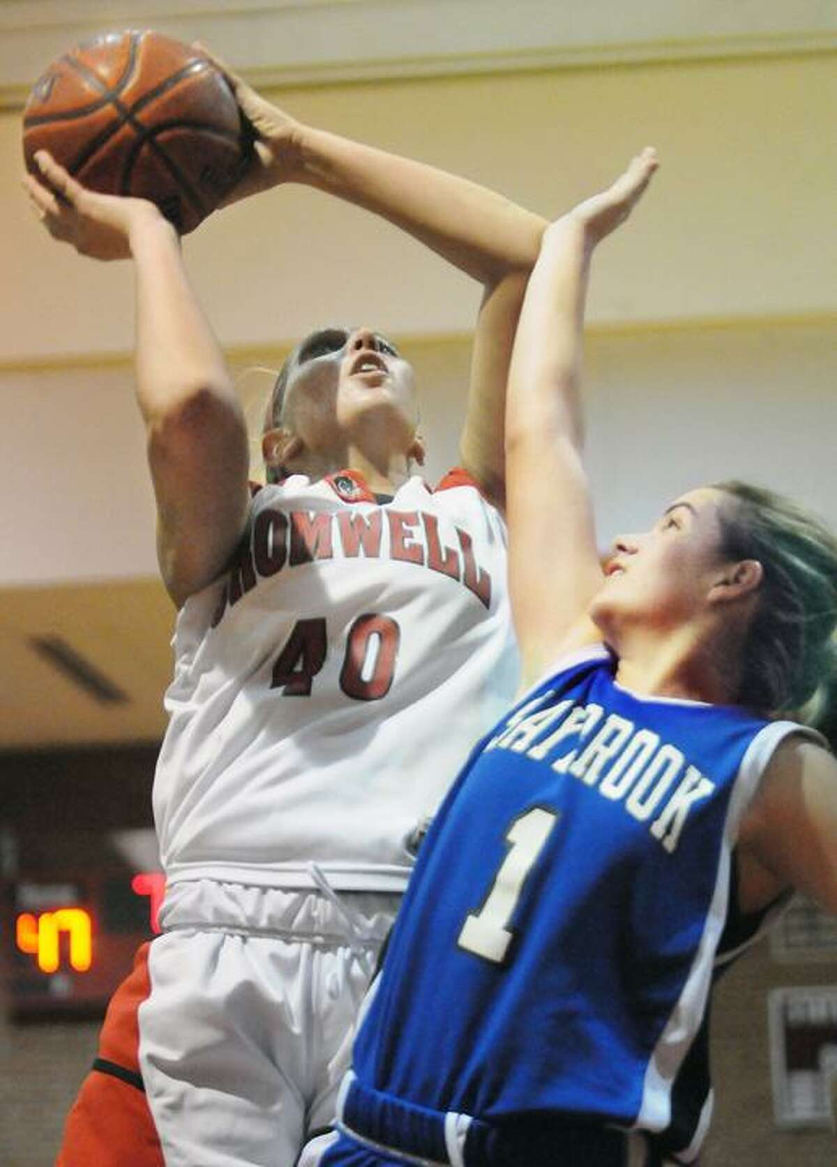 The Middletown Press 2.21.12 Cromwell's Janelle Harrison goes up for a shot against Old Saybrook's Paige Trabucchi in the fourth quarter Tuesday at Valley Regional in Deep River. Cromwell, #2 defeated the the Old Saybrook Rams #6 58-37 in Shoreline Conference semi-final game.