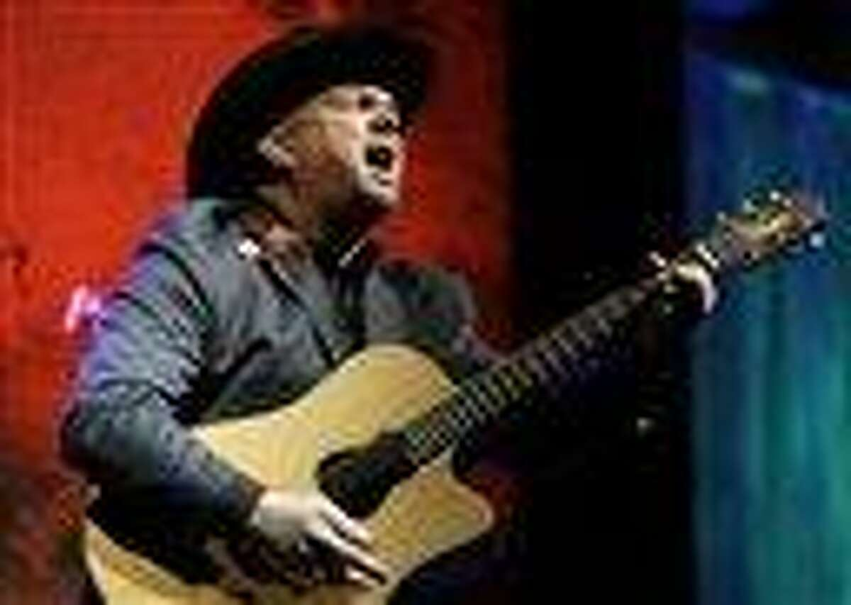 """Garth Brooks singing """"Papa Loved Mama,"""" a song written by Kim Williams, as Williams is inducted into the Nashville Songwriters Hall of Fame in Nashville. AP Photo/Mark Humphrey"""