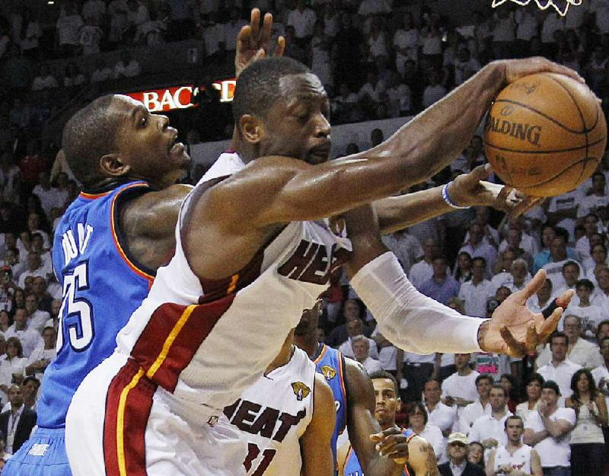 ASSOCIATED PRESS Miami Heat shooting guard Dwyane Wade (3) and Oklahoma City Thunder small forward Kevin Durant (35) chase a rebound during the second half at Game 4 of the NBA Finals Tuesday in Miami. The Heat won 104-98.