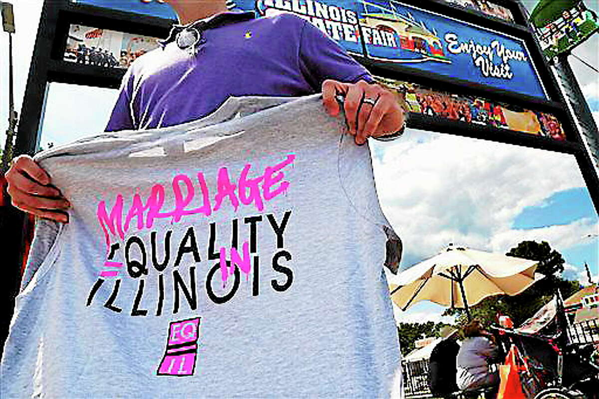 """In this Aug. 14, 2013 file photo, Randy Hannig of Equality Illinois, hands out shirts supporting gay marriage at the Illinois State Fair in Springfield, Ill. Minneapolis Mayor R.T. Rybak is hitting the road to promote his state's new gay marriage law. He is traveling to Chicago on Thursday, Sept. 5 to launch a """"Marry in Minneapolis"""" campaign in the hopes that Illinois gay and lesbian couples will do just that. Illinois has not passed a gay marriage law, an issue is scheduled to come before state lawmakers again this fall. AP Photo/Stacy Bengs,"""