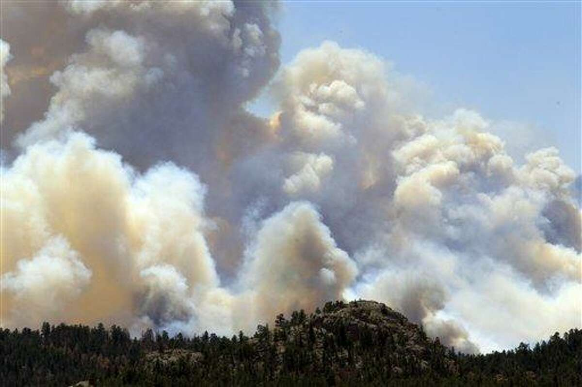 Smoke roils over a ridge east of Red Feather Lakes, Colo., as a stubborn wildfire continues to burn Sunday in northern Colorado. Crews are facing powerful winds as they battle the blaze that has scorched about 86 square miles of mountainous forest land and destroyed at least 181 homes, the most in state history. Associated Press
