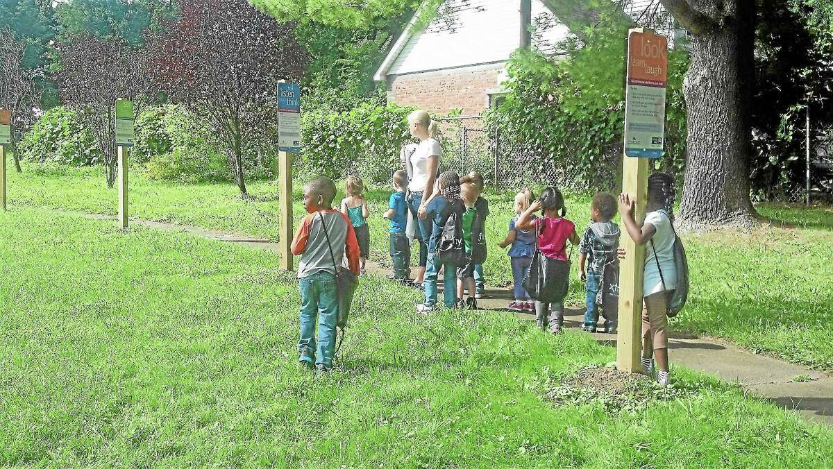Kristen Zajac's preschool class from the Middlesex YMCA listen to instructions on the Born Learning Trail at Macdonough Elementary School.