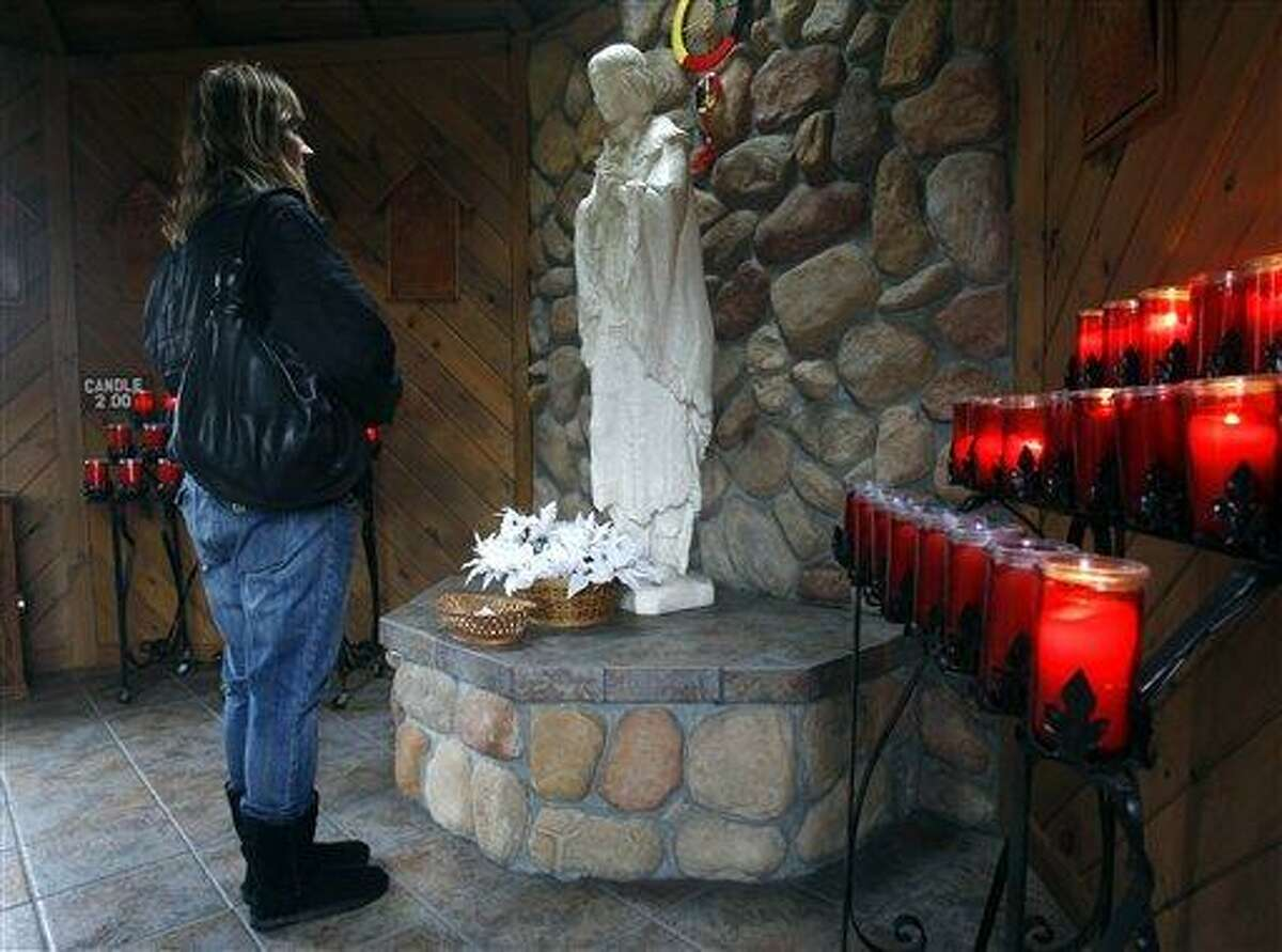 In this Wednesday, Dec. 21, 2011 file photo, Phyllis Tessitore of Amsterdam, N.Y., says a prayer in front of a statue of the the Blessed Kateri Tekakwitha at the National Kateri Shrine and Indian Museum in Fonda, N.Y. On Sunday, Oct. 21, 2012 the Vatican will formally recognize Tekakwitha, a 17th-century Mohawk Indian who spent most of her life in what is now upstate New York, as a saint. (AP Photo/Mike Groll)