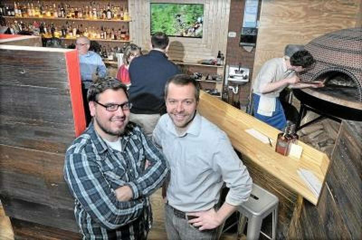 Catherine Avalone/The Middletown Press Kevin Wirtes, of Harwinton, and Middletown resident Rich Garcia, co-owners of Krust wood-fired pizza and bourbon bar at 686 Main St. in Middletown, opened its restaurant Jan. 17. It serves a variety of wood-fired pizzas created in 5,800-pound Forno Bravo brick oven and over 200 alcoholic options.