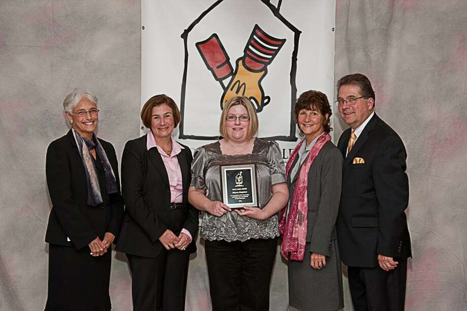Submitted photo Laura Phillips Ward (second from left), president of the Ronald McDonald House Charities of Connecticut and Western Massachusetts, presents Memorial Elementary School third-grade teacher Allyson Singleton, center, with a plaque commemorating her RMHC Local Hero Award, which recognizes 10 outstanding area teachers each year. Joining them are East Hampton Public Schools Superintendent Judith Goldman, left, school Principal Karen Fitzsimmons, second from right, and East Hampton Public Schools Assistant Superintendent Kevin Reich, right. / Anthony F. Esposito Jr. © 2011