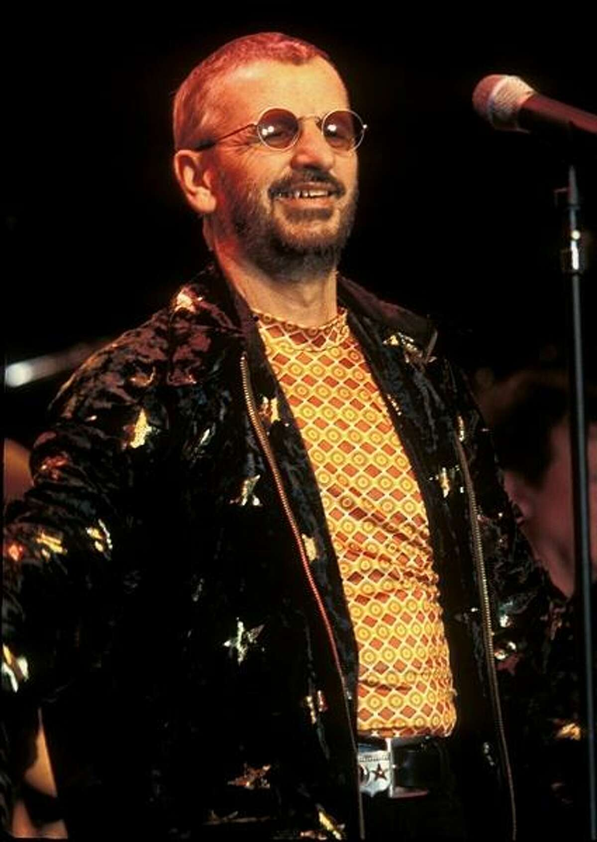 Former Beatle drummer Ringo Starr is shown performing on stage during a