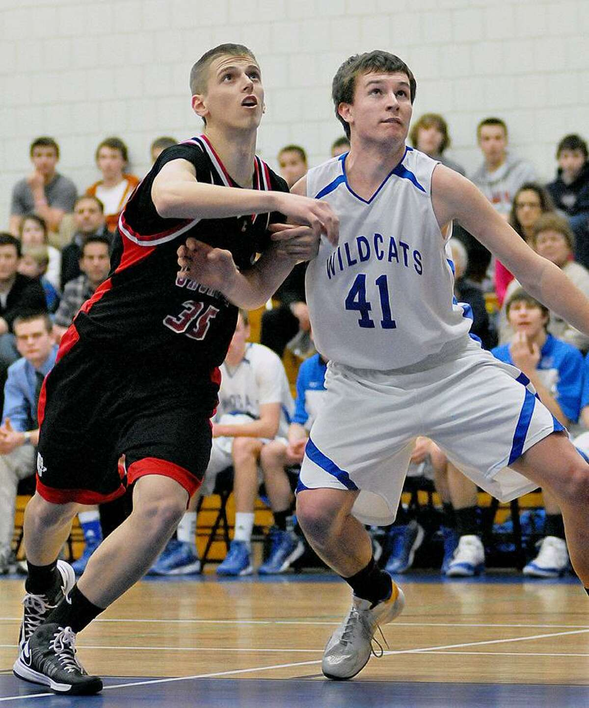 Catherine Avalone/The Middletown Press Cromwell senior forward Ael Cecunjanin battles Lyme-Old Lyme sophomore center Liam Corrigan in the paint Tuesday night. The Lyme-Old Lyme Wildcats defeated Cromwell Panthers 56-46 in the Shoreline Semi-Final game in Old Lyme.