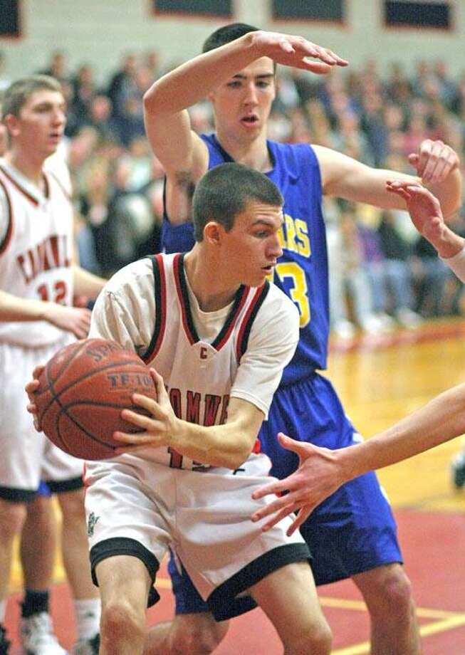 """Special to the Press 02.20.12 Haddam-Killingworth's Erik Carlson scores over Cromwell's Pat Sirois in Friday's game. Cromwell won, 52-43 . To buy a glossy print of this photo and more, visit <a href=""""http://www.middletownpress.com"""">www.middletownpress.com</a>. / a"""