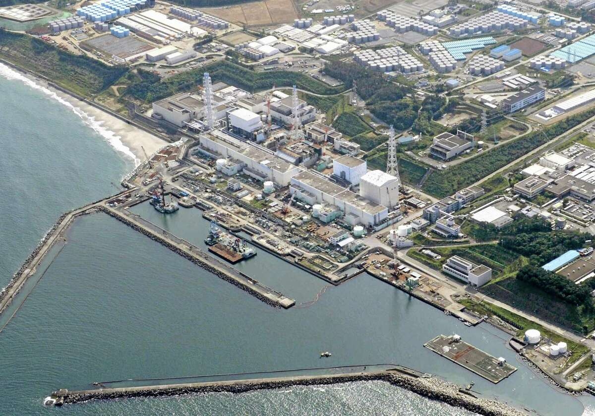 """This aerial photo taken on Aug. 31, 2013, shows the Fukushima Dai-ichi nuclear plant at Okuma town in Fukushima prefecture, northeastern Japan. Just weeks after Japanese officials acknowledged that radioactive water has been seeping into the Pacific from the tsunami-crippled nuclear power plant for more than two years, new revelations of leaks of contaminated water from storage tanks have raised further alarm. The government announced the week of Sept. 1, 2013 that it would contribute 47 billion yen ($470 million) to build an underground """"ice wall"""" around the reactor and turbine buildings and develop an advanced water treatment system. (AP Photo/Kyodo News) JAPAN OUT, MANDATORY CREDIT"""
