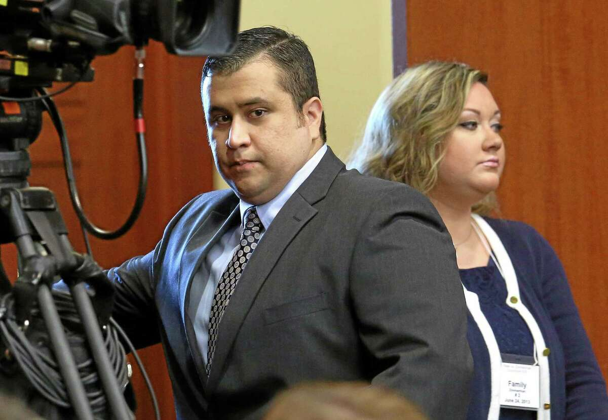 FILE - In this Monday, June 24, 2013 file photo, George Zimmerman, left, arrives in Seminole circuit court with his wife, Shellie, on the 11th day of his trial, in Sanford, Fla. George Zimmerman's wife filed for divorce Thursday, Sept. 5, 2013 less than two months after her husband was acquitted of murdering Trayvon Martin and a week after she pleaded guilty to perjury in his case. (AP Photo/Orlando Sentinel, Joe Burbank, Pool, File)