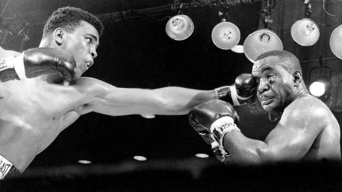 """Challenger Cassius Clay throws a straight left to the face of Charles """"Sonny"""" Liston in third round of their heavyweight championship fight at Convention Hall in Miami Beach, Fla., on Feb. 25, 1964. The 22-year-old Clay, of Louisville, Ky., defeated Liston in a technical knockout to become the world heavyweight champion. (AP Photo)"""