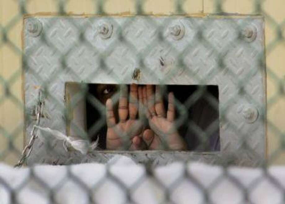 "FILE - In this Dec. 4, 2006 file photo reviewed by a U.S. Dept of Defense official, a detainee shields his face as he peers out through the so-called ""bean hole"" which is used to pass food and other items into detainee cells, at Camp Delta detention center, Guantanamo Bay U.S. Naval Base, Cuba. Lt. Col. Samuel House said Friday, April 26, 2013 that 97 men are now on strike, up three from the day before. He says 19 of them are receiving liquid nutrients through a nasal tube to prevent dangerous weight loss. Another five are under observation at the hospital on the U.S. base in Cuba. The hunger strike began in February 2013, with prisoners protesting conditions and their indefinite confinement. The U.S. holds 166 prisoners at Guantanamo, most without charges. (AP Photo/Brennan Llinsley) Photo: AP / AP"