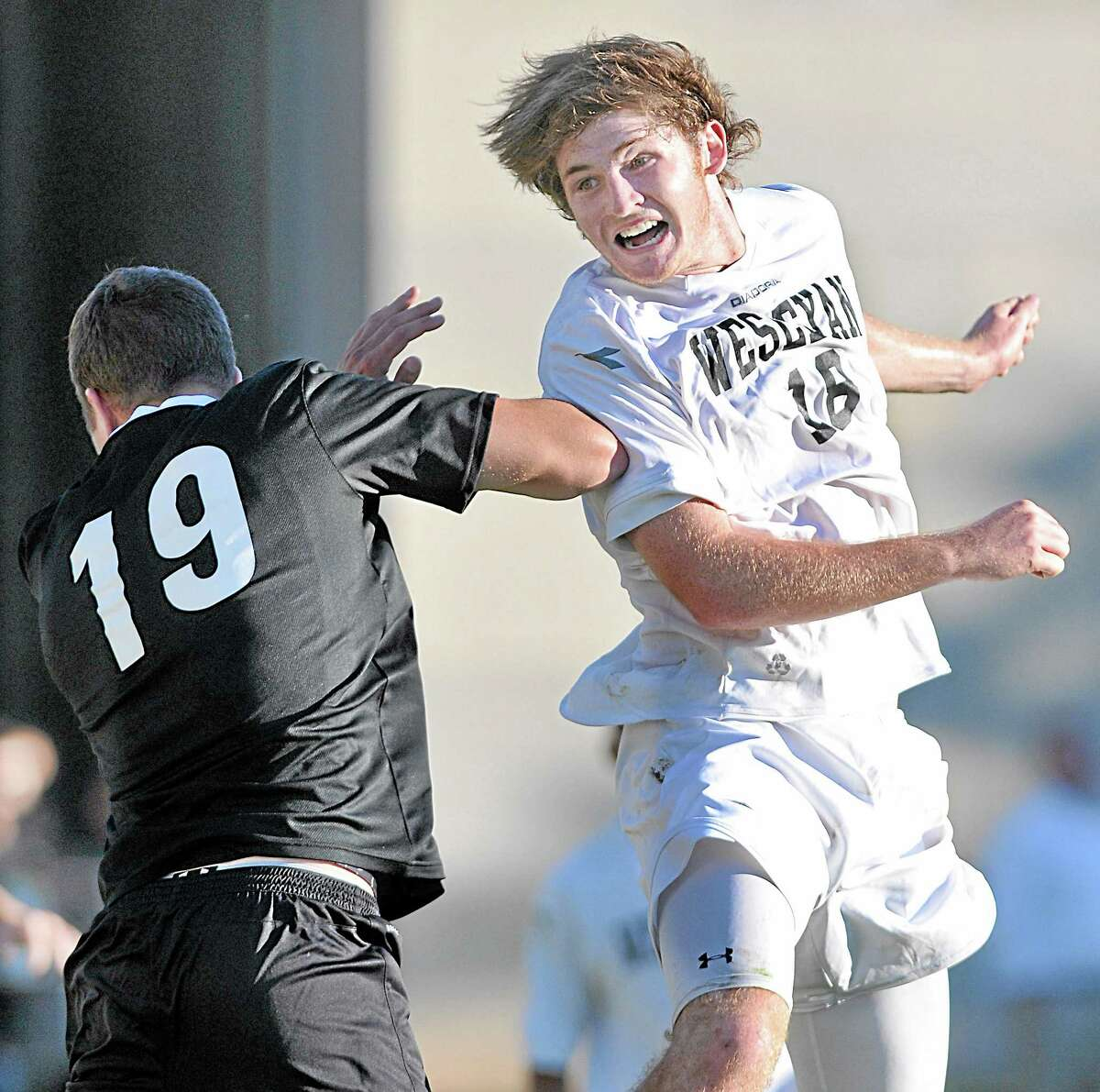 Wesleyan freshman Charlie Gruner looks to the goal after a header up and over Framingham State University senior co-captain Ryan Boughter in the second half of Wednesday's game at Jackson Field in Middletown. The Cardinals defeated the Rams 3-0.