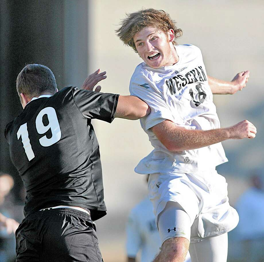 Wesleyan freshman Charlie Gruner looks to the goal after a header up and over Framingham State University senior co-captain Ryan Boughter in the second half of Wednesday's game at Jackson Field in Middletown. The Cardinals defeated the Rams 3-0. Photo: Catherine Avalone — The Middletown Press  / TheMiddletownPress