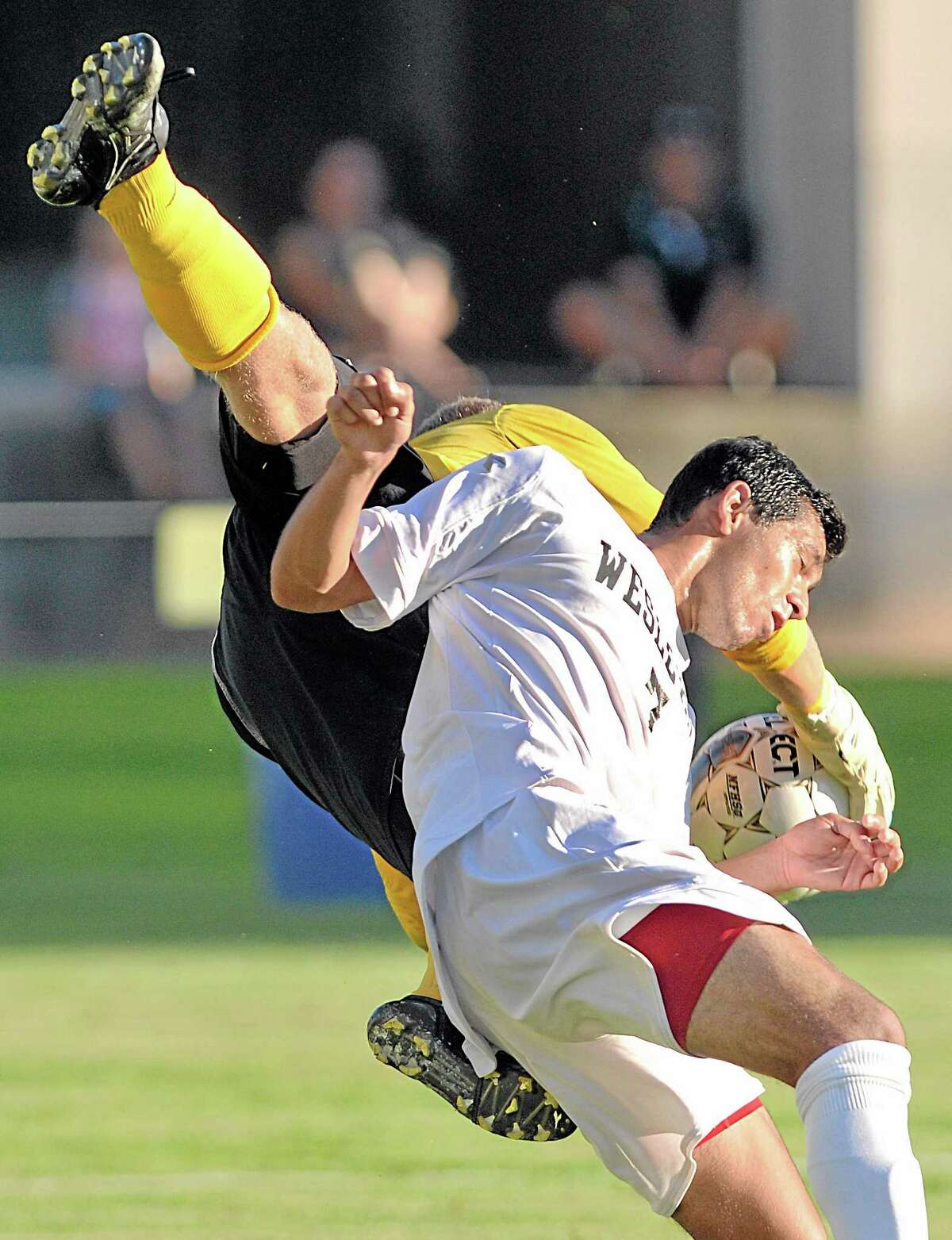 Wesleyan junior Omar Bravo collides with Framingham State University junior goalie William Levitsky battling for possession in the second half of Wednesday's game at Jackson Field. The Cardinals defeated the Rams 3-0.