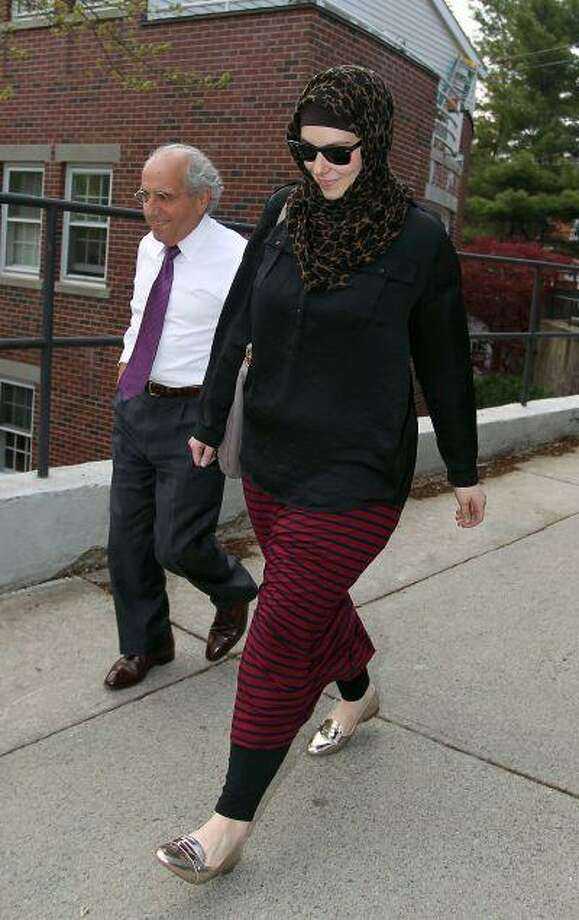 In this April 29 file photo, Katherine Russell, wife of Boston Marathon bomber suspect Tamerlan Tsarnaev, right, leaves the law office of DeLuca and Weizenbaum with Amato DeLuca, in Providence, R.I. Relatives of Tsarnaev, the older of the brothers suspected in the Boston Marathon bombing, will claim his body now that his wife has agreed to release it, an uncle said as officials in the U.S. and Russia deepened their investigations into him. (AP Photo/Stew Milne, File) Photo: ASSOCIATED PRESS / AP2013