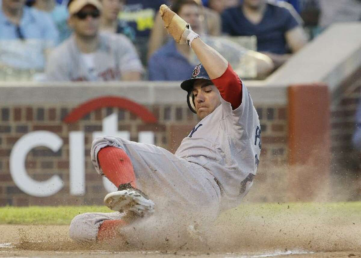 ASSOCIATED PRESS Boston Red Sox's Scott Podsednik scores on a double hit by Dustin Pedroia during the first inning of Sunday's game against the Chicago Cubs at Wrigley Field in Chicago. The Red Sox won 7-4.