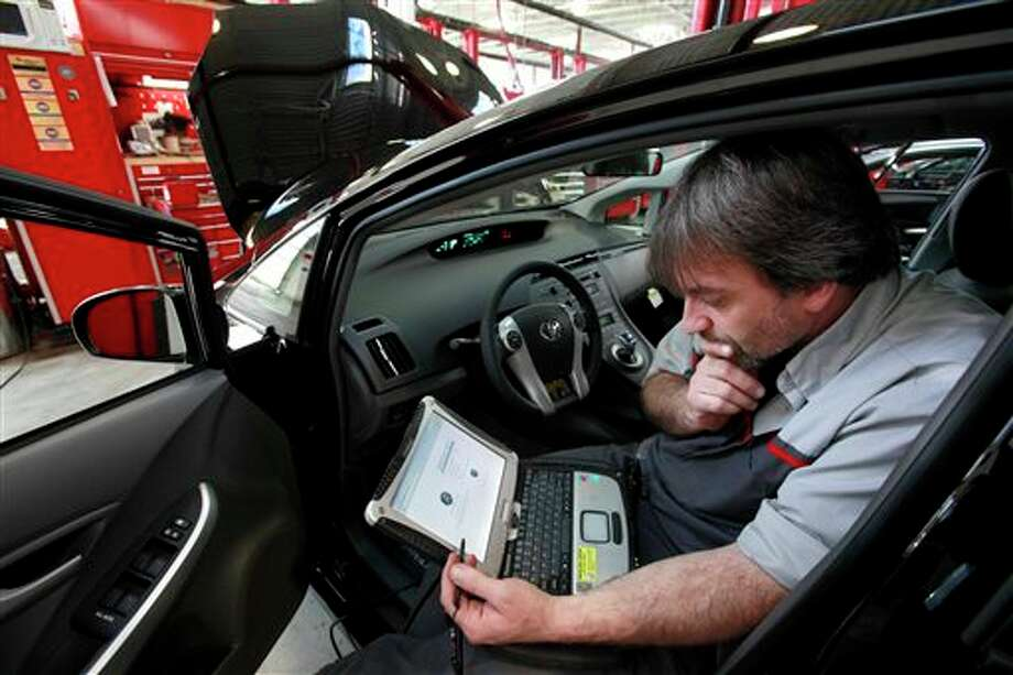 FILE - In this Feb. 9, 2010 file photo, master diagnostic technician Kurt Juergens, of Foxborough, Mass., uses a laptop computer to diagnose and repair the brake system on a 2010 Toyota Prius in the repair shop of a Toyota dealership, in Norwood, Mass. A pair of hackers maneuvered their way into the computer systems of a 2010 Toyota Prius and 2010 Ford Escape through a port used by mechanics. The hackers showed that they could slam on the brakes at freeway speeds, jerk the steering wheel or even shut down the engine, all from their laptop computers. The work demonstrates vulnerabilities with the growing number of car computers, about 20 on older models and up to 70 on sophisticated luxury cars. (AP Photo/Steven Senne, File) Photo: AP / AP