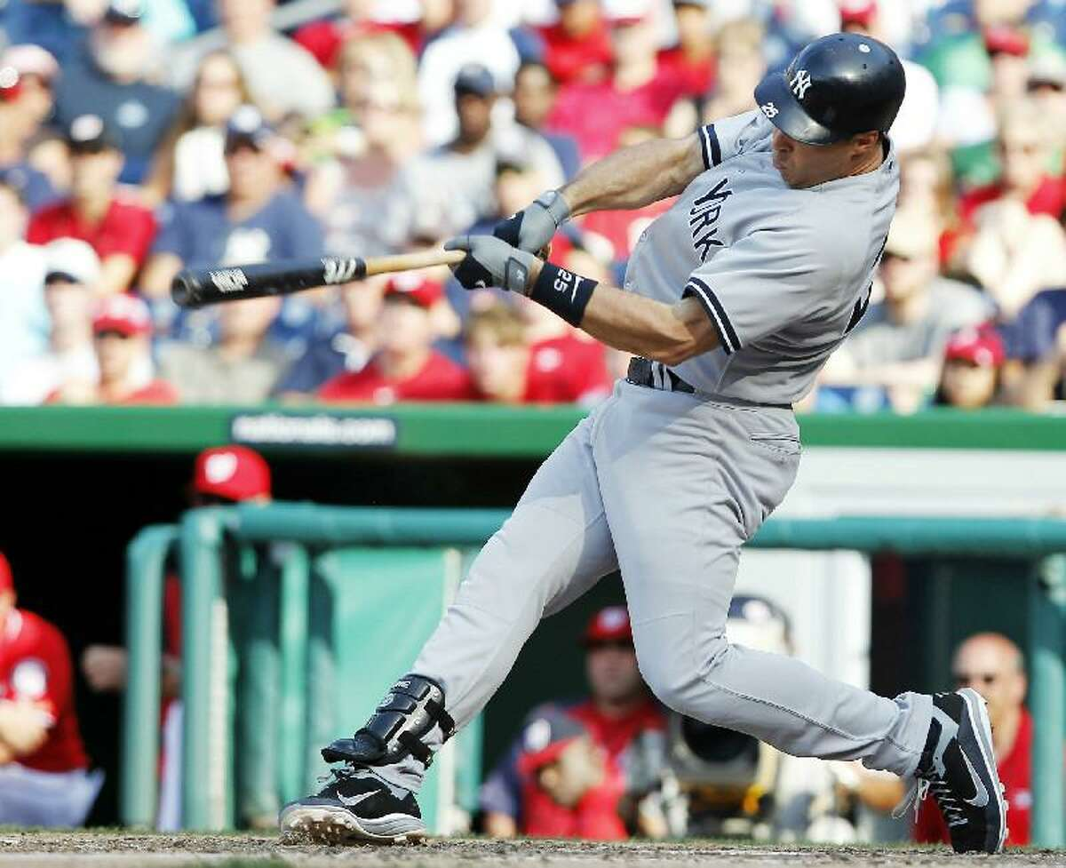 ASSOCIATED PRESS New York Yankees first baseman Mark Teixeira swings on a two-run double during the 14th inning Saturday's game against the Washington Nationals at Nationals Park in Washington. The Yankees won 5-3 in 14 innings.