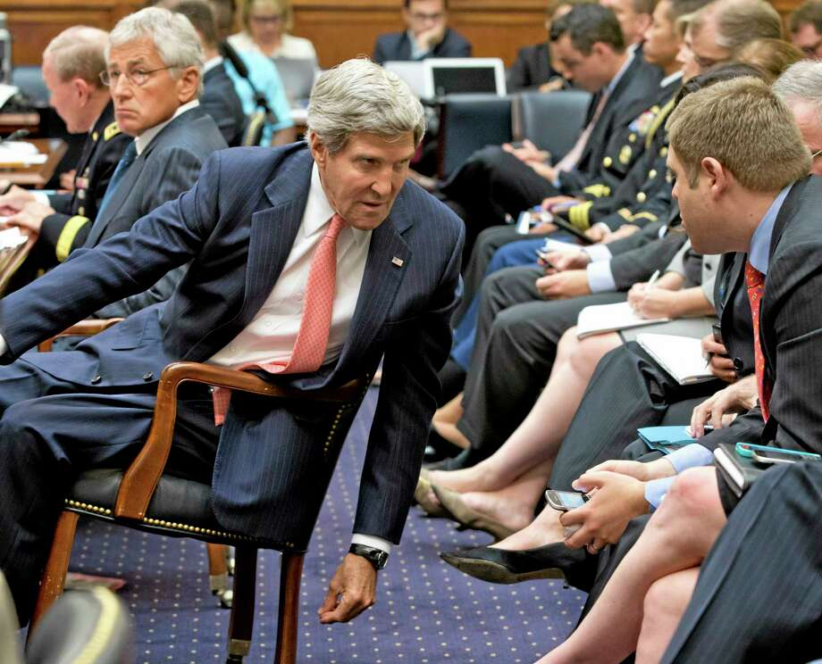 Secretary of State John Kerry leans over to confer with his advisers, on Capitol Hill in Washington, Wednesday, Sept. 4, 2013, as he testified before the House Foreign Affairs Committee to advance President Barack Obama's request for congressional authorization for military intervention in Syria, a response to last month's alleged sarin gas attack in the Syrian civil war. Defense Secretary Chuck Hagel is at left.  (AP Photo/J. Scott Applewhite) Photo: AP / AP