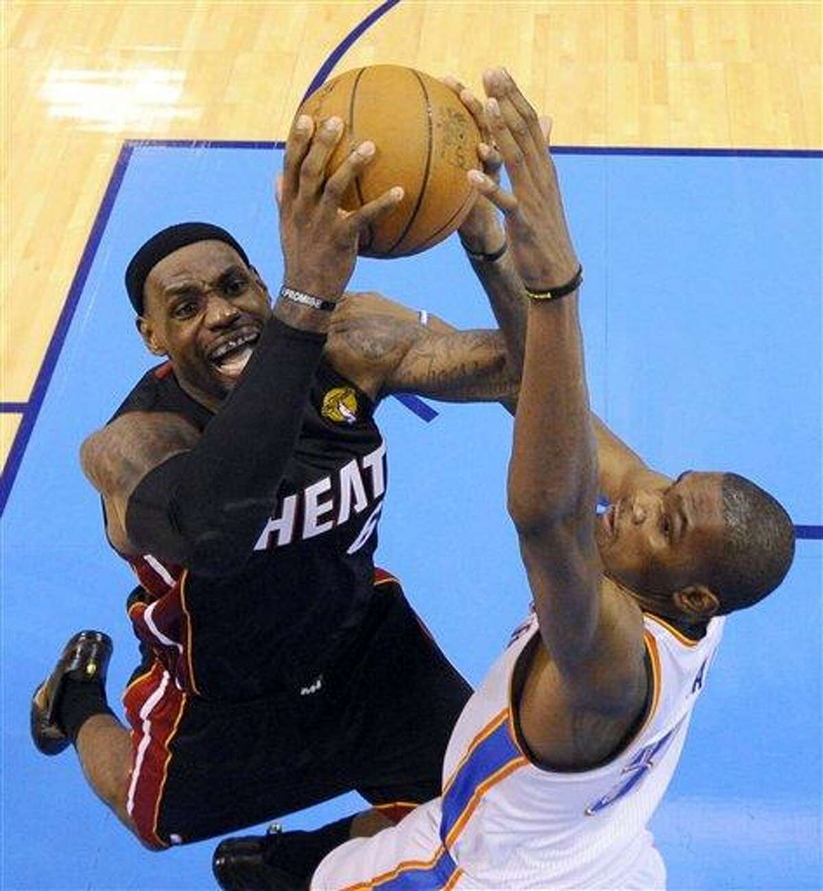 Miami Heat small forward LeBron James is defended by Oklahoma City Thunder small forward Kevin Durant (35) during the second half at Game 2 of the NBA finals basketball series, Thursday, June 14, 2012, in Oklahoma City. The Heat won 100-96. (AP Photo/Larry W. Smith, Pool)