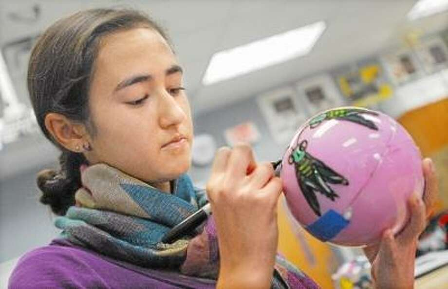 CATHERINE AVALONE/THE MIDDLETOWN PRESS Middletown High School senior Ava Varszegi, 17 puts the finishing touch on a praying mantis Christmas ornament during art class. Varszegi chose to embellish the five and a half inch plastic ornament with the state insect.
