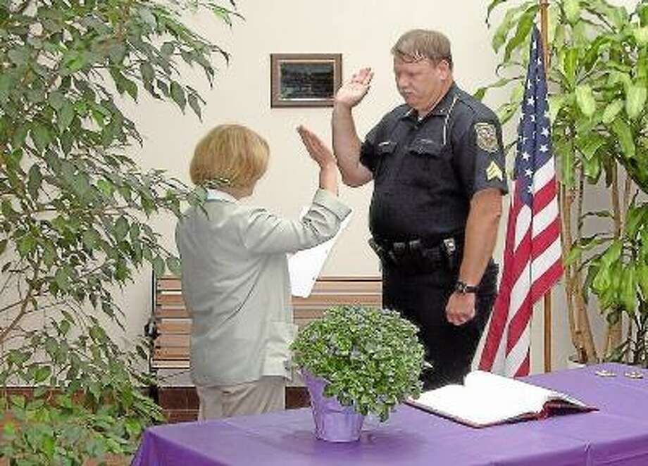 Photo Credit/Cromwell Police Dept. Town Clerk Darlene DiProto swears in Sergeant Wren on July 11th, 2005. Wren retired Tuesday.