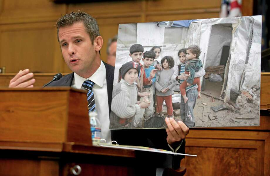 House Foreign Affairs Committee member Rep. Adam Kinzinger, R-Ill. hold up a photograph of Syrian children as he speaks on Capitol Hill in Washington, Wednesday, Sept. 4, 2013, during the committee's hearing on Syria. (AP Photo/Carolyn Kaster) Photo: AP / AP