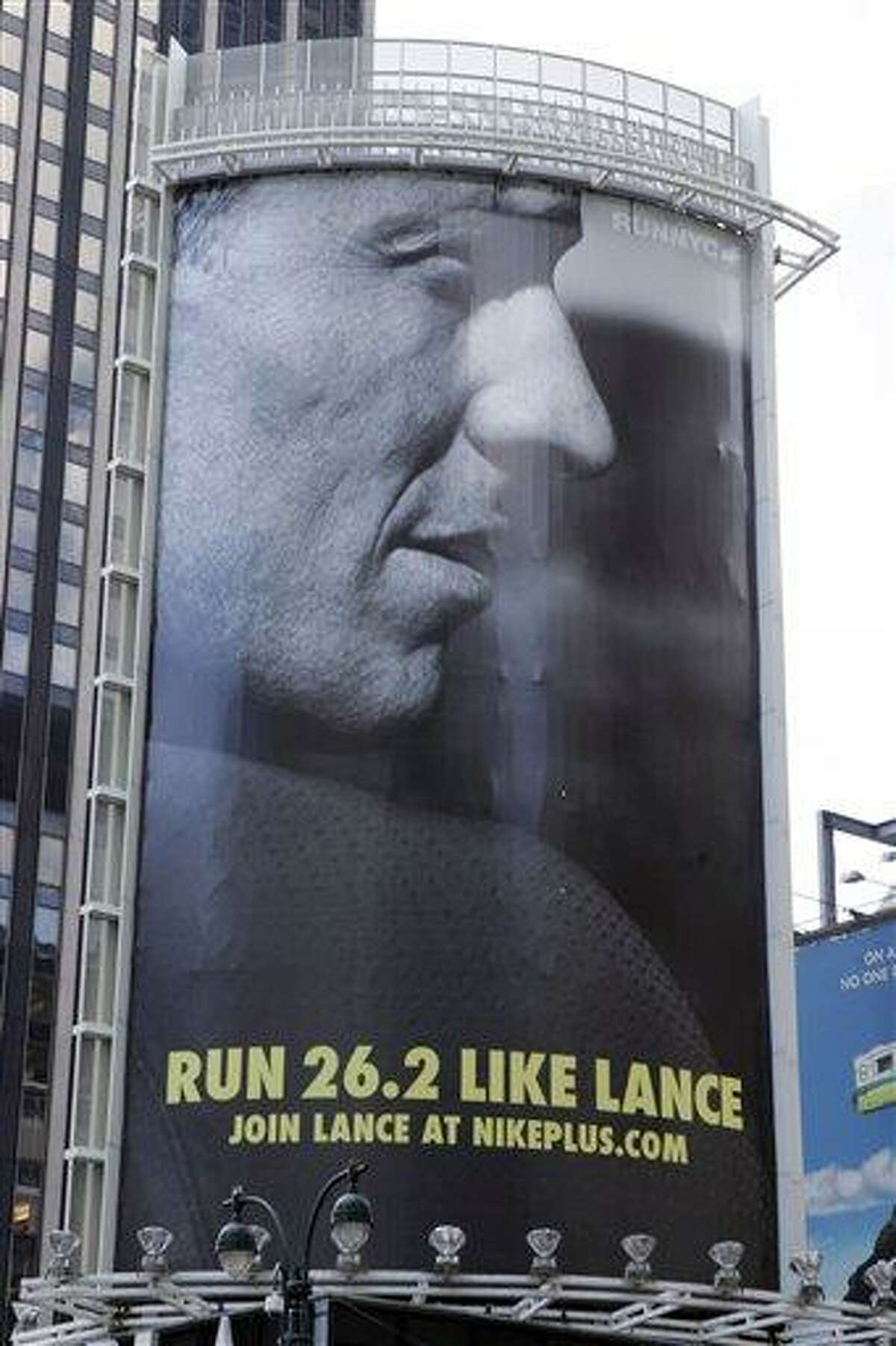 """In an 80-foot billboard at 34th Street and 7th Avenue in Manhattan, Lance Armstrong and Nike challenge New Yorkers to """"Run Like Lance"""" in a 2006 file photo. Nike said Wednesday that it is severing ties with Armstrong, citing insurmountable evidence that the cyclist participated in doping and misled the company for more than a decade. Associated Press"""