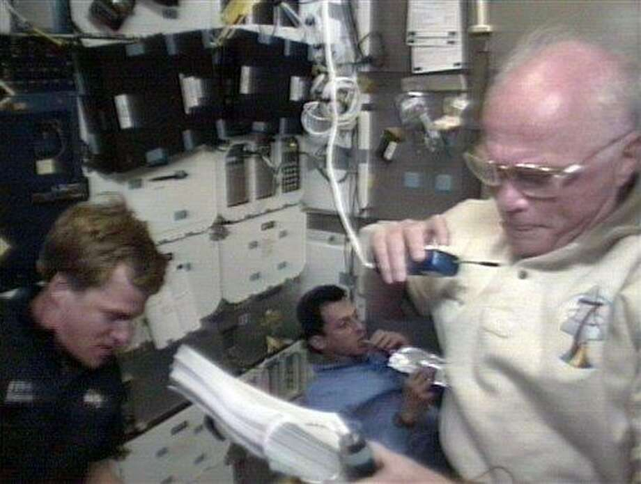 In this 1998 image made from video provided by NASA, U.S. Sen. John Glenn, right, speaks to mission control during an experiment, assisted by astronaut Scott Parazynski, left, as Spanish astronaut Pedro Duque eats from a food packet aboard the space shuttle Discovery. Associated Press Photo: AP / AP1998