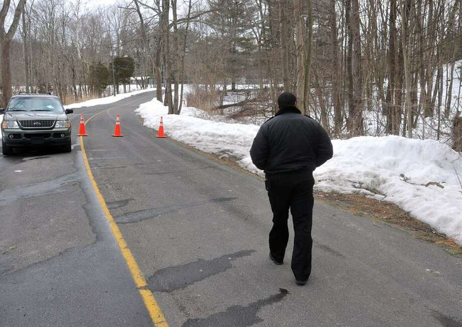 Sandy Hook-- A security guard walks back to his vehicle as he guards the entrance to the Sandy Hook Elementary School. The roadway was still blocked and no one was permitted to drive to the school.  Photo-Peter Casolino 02/22/12