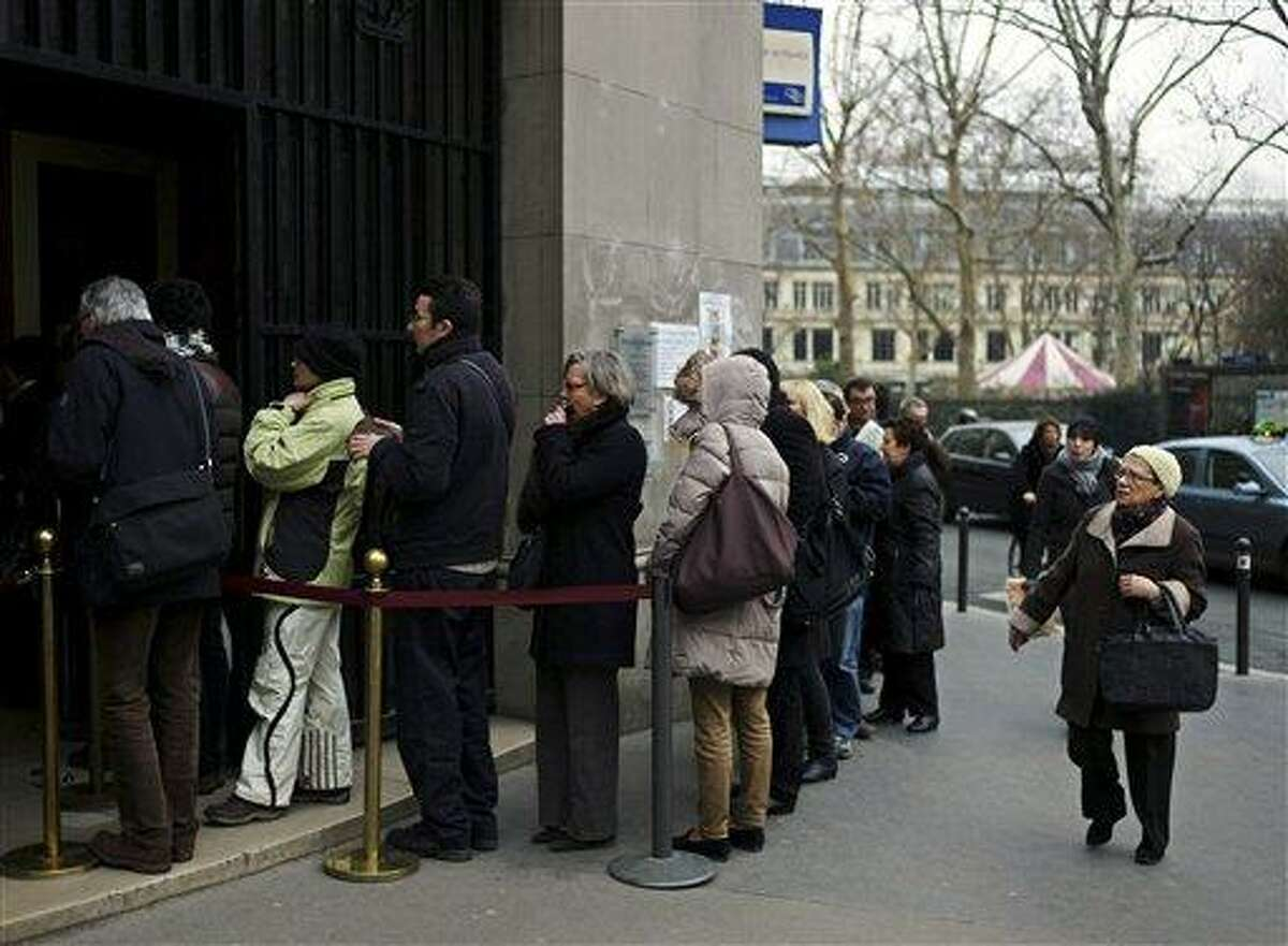 People line up along a branch of the Banque de France to convert French francs to euros in Paris, Friday. Six centuries after the first one was minted and a decade after they went out of circulation, the last French francs are being exchanged for euros, severing France's final link to its former national currency. Associated Press