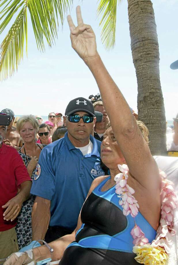 In this photo provided by the Florida Keys News Bureau, Diana Nyad, right, gestures a V for victory after completing a 111-mile swim from Cuba to Key West, Fla. Nyad, 64, is the first swimmer to cross the Florida Straits without the security of a shark cage. The swim took Nyad 52 hours and 54 minutes, according to a support team member. (AP Photo/Florida Keys Bureau, Andy Newman) Photo: AP / Florida Keys News Bureau