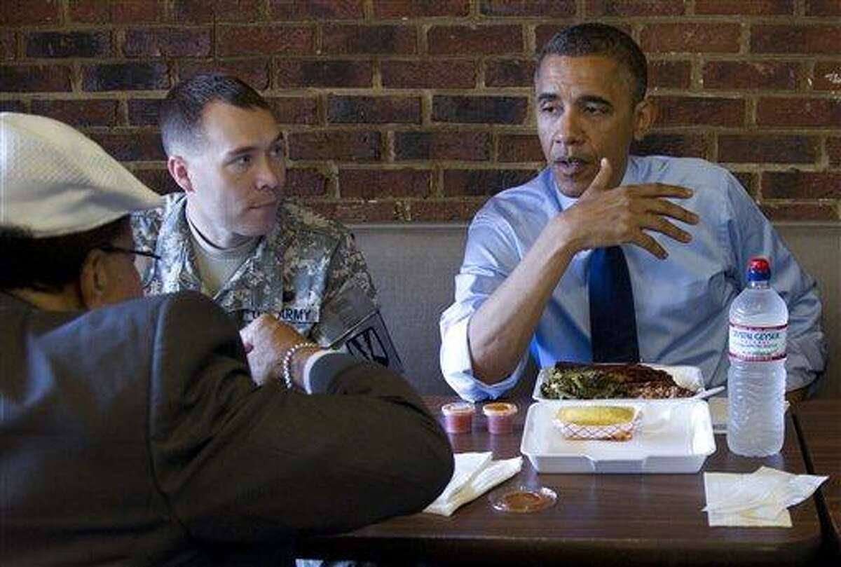 President Barack Obama visits a Kenny's BBQ restaurant with Army First Lt. William Edwards, a 2012 Military Fatherhood Award Winner, second from left, and Nurney Mason owner of Mason's Barber Shop, left back to camera, Wednesday in Washington. Associated Press