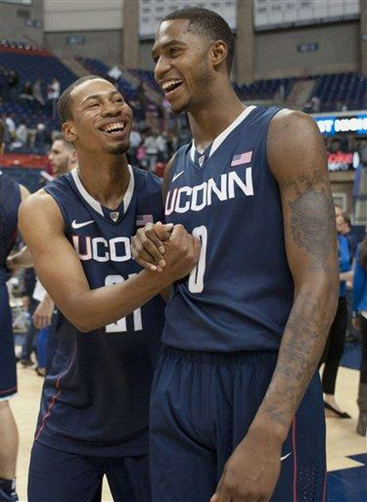 Connecticut's Omar Calhoun, left, celebrates with teammate Phillip Nolan, right after winning the slam dunk competition at the NCAA college basketball team's First Night event in Storrs, Conn., Friday, Oct. 12, 2012. (AP Photo/Jessica Hill)