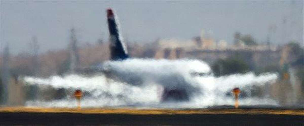 An airliner is distorted by the heat waves rising up from the north runway at Sky Harbor International Airport in Phoenix on Friday, June 28, 2013, the hottest day of the year so far. (AP Photo/The Arizona Republic, Tom Tingle)