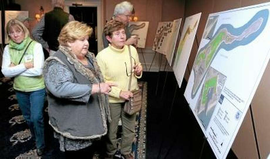 Left to right, Felise Cressman of Chester, Linda Knightly of Old Saybrook and Jeanne Munnelly of Old Lyme look over maps of Plum Island prior to a public hearing concerning the sale of Plum Island at the Saybrook Point Inn and Spa in Old Saybrook on 10/17/2012. Photo by Arnold Gold/New Haven Register    AG0467C