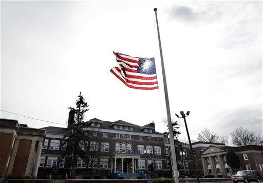 An American flag flies at half-staff in front of The Whitney E. Houston Academy of Creative and Performing Arts in East Orange, N.J. As a young girl, Houston attended what was known then as the Franklin School. Houston, who ruled as pop music's queen until her majestic voice and regal image were ravaged by drug use, erratic behavior and a tumultuous marriage to singer Bobby Brown, died Saturday. She was 48.  Associated Press Photo: ASSOCIATED PRESS / AP2012