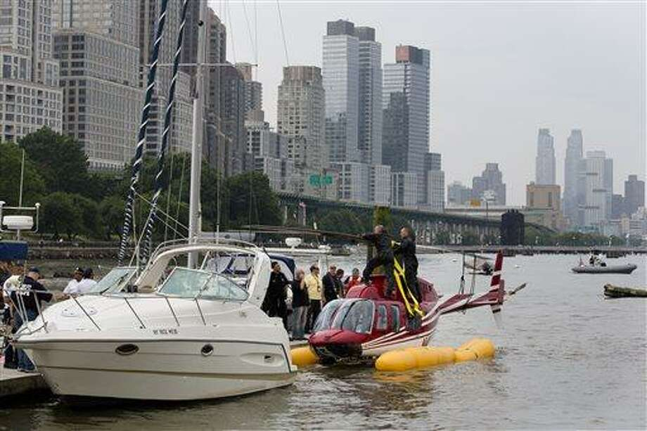 A helicopter rests on a pontoon at the 79th Street Boat Basin after emergency landing over the Hudson river, Sunday, June 30, 2013, in New York. New York authorities say a helicopter carrying four Swedish tourists landed in the Hudson River off Manhattan Sunday, but everyone has been rescued. (AP Photo/John Minchillo) Photo: AP / FR170537 AP