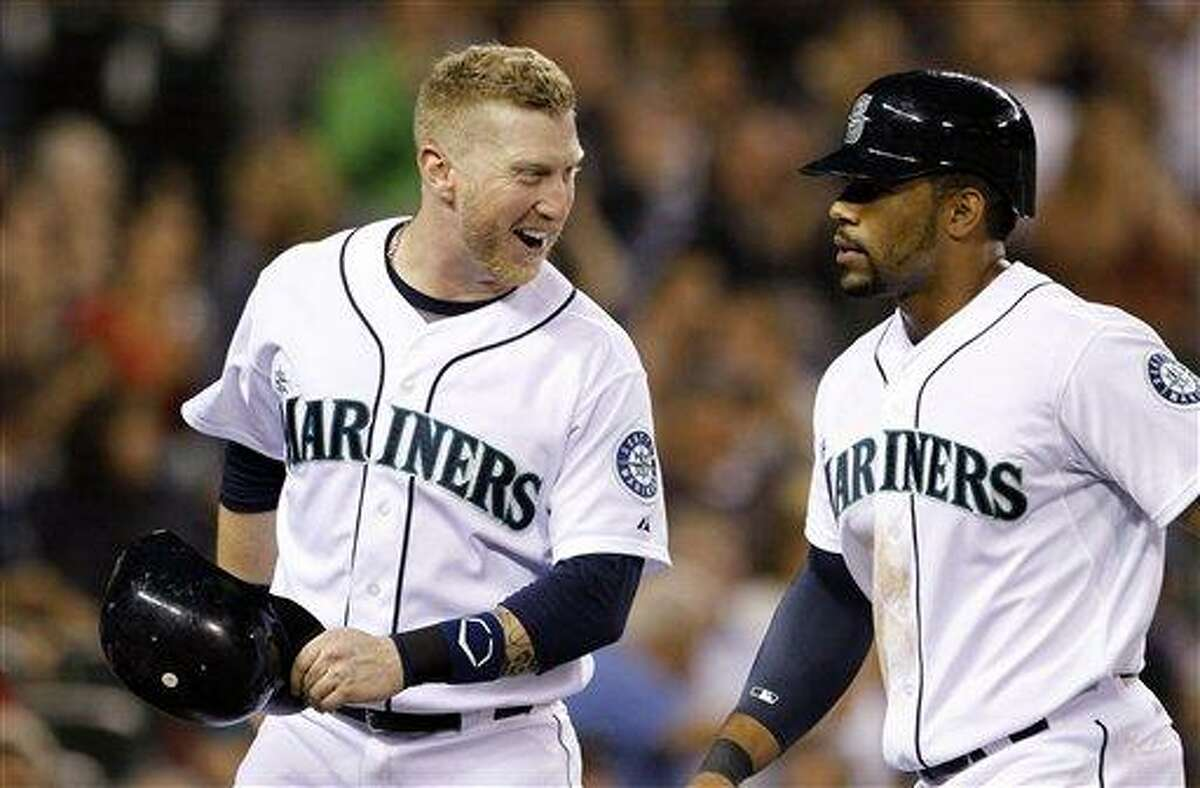 Seattle Mariners' Mike Carp, left, smiles back at Eric Thames after the pair scored against the Boston Red Sox in the fourth inning of a baseball game Wednesday, Sept. 5, 2012, in Seattle. (AP Photo/Elaine Thompson)