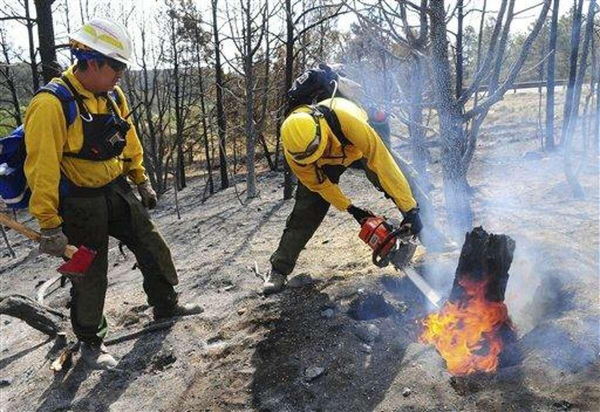 Arizona's Hopi 5 Hotshot Ian Nuvamsa, at left, watches as teammate Peterson Hubbard cuts a burning stump Monday while battling the Little Bear fire near Ruidoso, N.M. Associated Press